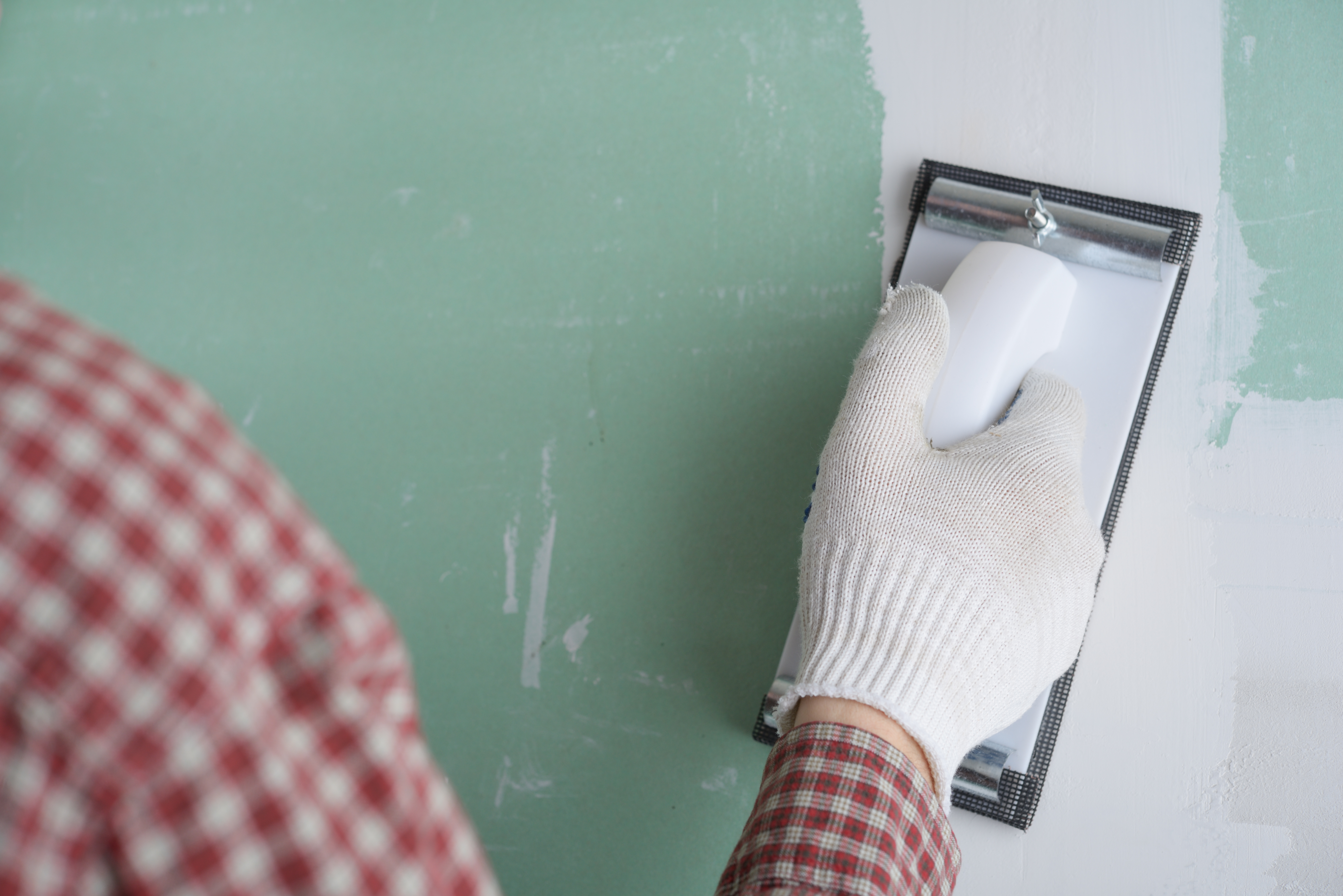Contractor sanding the drywall mud using sand trowel